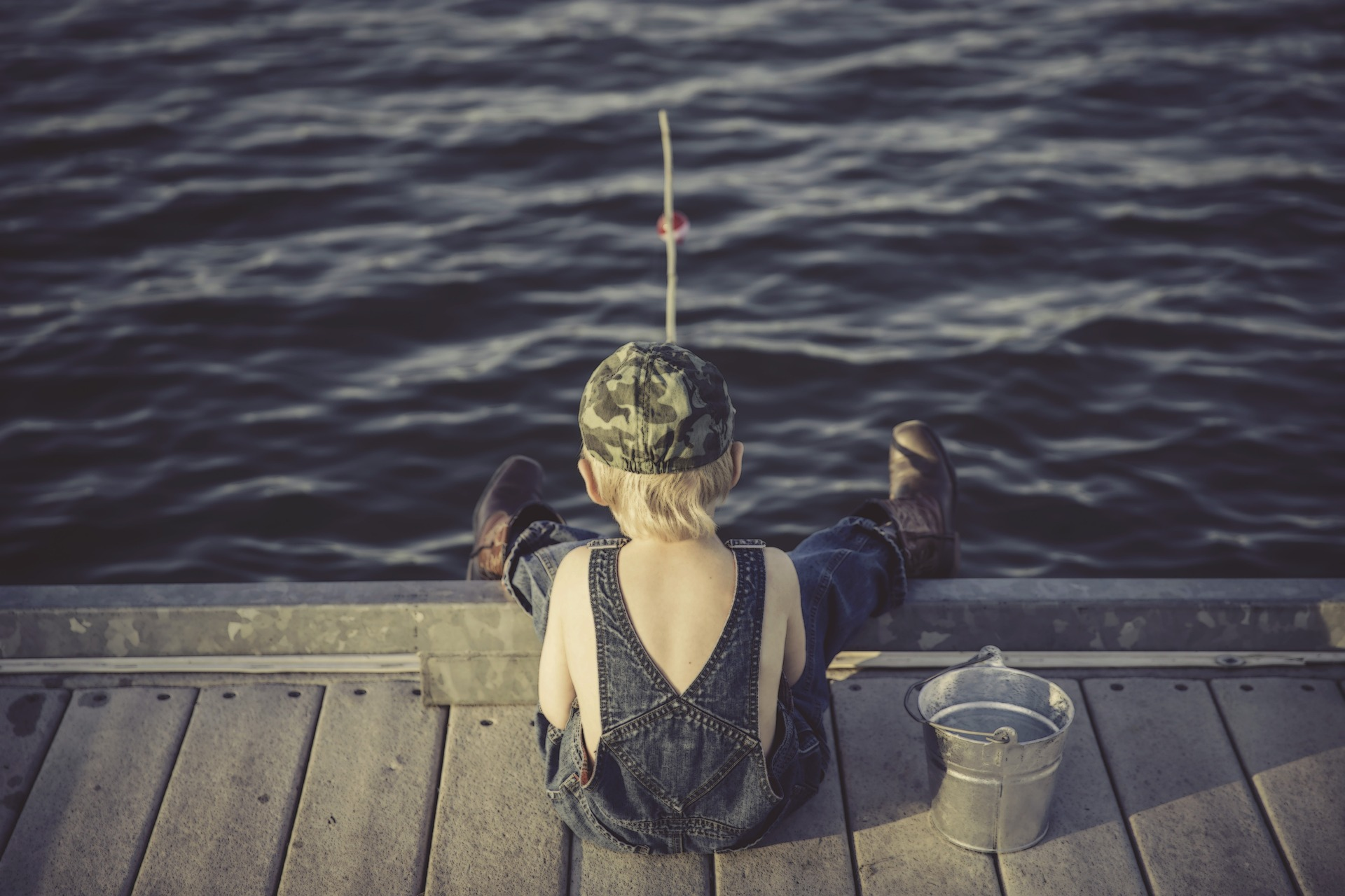 Image of a young boy fishing off a dock.
