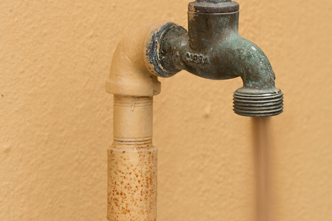 Cropped image of dirty water flowing from a tap.